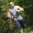 Young mrunning in woods — Stock Photo #36693515