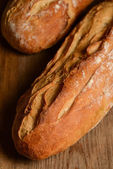 French crusty bread, isolated on a wooden plank background — Stock Photo