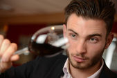 Young man with redwine glasses at celebration or party — Stock Photo