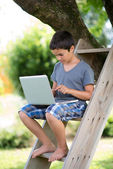 Child playing on the computer with headphones outdoor — Stock Photo