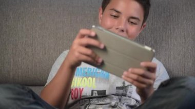 Teenager- Young boy playing from digital tablet — Stock Video