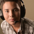 Portrait of Smiling Teenage Boy Listening to Musicon a brown bac — Stock Photo #51173373