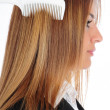 Woman combing her long hair with hairbrush — Stock Photo #26522747