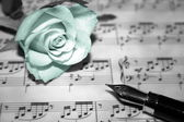 Rose on musical notes page — Stock Photo