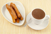A churro with chocolate in cup, Spanish doughnut — Stock Photo