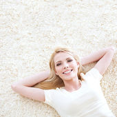 Beautiful blond woman posing lying down on a carpet. — Stock fotografie