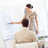 Smiling architect presenting her project to a colleague. — Stock Photo