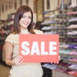 Shop Assistant Holding the 'Sale' Notice — Stock Photo #34735161