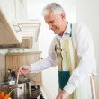 Smiling Senior Man Cooking at Home — Stock Photo #34735341