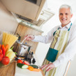 Senior Man Cooking at Home — Stock Photo #34735405