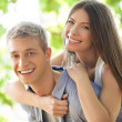 Portrait of a smiling young couple in an outdoor setting. — Stock Photo