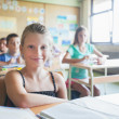 Smiling Schoolgirl Sitting in the Classroom — Foto Stock