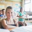 Smiling Schoolgirl Sitting in the Classroom — Lizenzfreies Foto