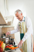 Smiling Senior Man Cooking at Home — Stock Photo