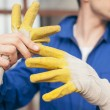 Builder Taking Off Protective Gloves — Stock Photo #34753875