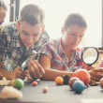 Постер, плакат: Astronomy Class: Students Examining Planet Models