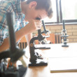 Biology Lesson: Boy Using a Microscope — Stock Photo #34755495