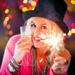 Woman holding a sparkler and a glass of champagne — Stock Photo #34755629