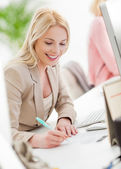 Smiling Businesswoman Writing at Her Desk — Stock Photo