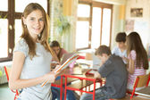 Smiling Girl Holding a Notebook at School — Stock Photo