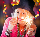 Woman holding a sparkler and a glass of champagne — Stok fotoğraf