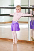 Young girl in ballet class against rail — Stock Photo