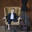 Portrait of stylish little boy sits in a chair near an old suitcase and dummy — Stock Photo #30115533