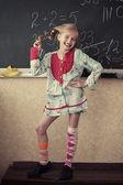 Funny girl near chalkboard — Stock Photo