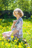 Young pregnant woman sit down on grass with yellow flowers — Stok fotoğraf