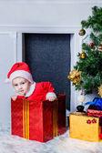 мальчик, одетый как санта, сидя в подарочной коробке — Стоковое фото