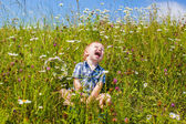 A boy sits next to the flowers and laughs — Stock Photo