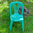 Green plastic chair In lawn — Stock Photo