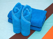 Blue towel roll on the bed. — Stock Photo