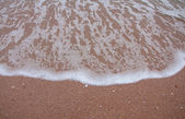 Wave of sea on the sandy beach — Stock Photo