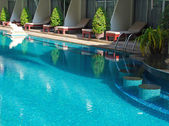 Blue water in hotel swimming pool with bar — Stock Photo