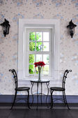 Iron chairs lamp with vase and window — Stock Photo