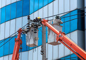 Electrician Man on Crane lifts. Electrical repairs on poles — Stockfoto