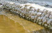 White sandbags for flood defense and it's reflection brown water — Stock Photo