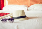 Straw hat and sunglasses on bed — Stock Photo
