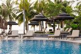 Beach chairs near swimming pool — Stock Photo