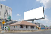 Large blank billboard on road with city view background — Photo