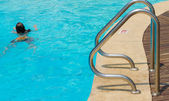 Blue swimming pool with staircase at hotel — Stock Photo