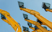 Excavator bucket on the end of a yellow hydraulic arm of a diggi — Stock Photo