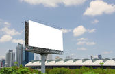 Large blank billboard on road with city view background — Stock Photo