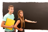 Woman pointing to the blackboard and man with book standing — Foto Stock