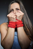 Beautiful young woman tied with the red rope — Stock Photo