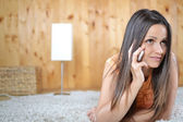 A young woman talking on her cell phone in her room — Stock Photo