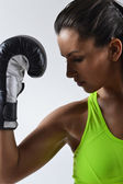 Beautiful fitness woman with the black boxing gloves — Stock Photo