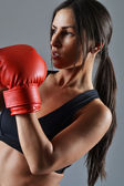 Beautiful fitness woman with the red boxing gloves — Stock Photo
