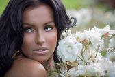 Brunette posing near white roses — Stock Photo